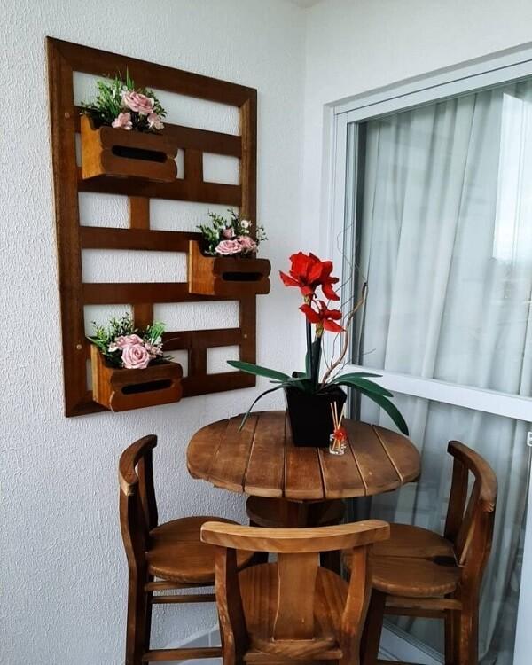 A floreira de parede de madeira se harmoniza com os móveis da varanda