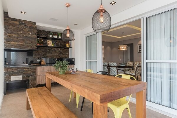 A parede com revestimento escuro e cadeiras amarelas se destacam na área gourmet rústica
