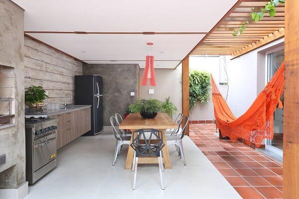 A rede de descanso laranja se destaca na área gourmet rústica