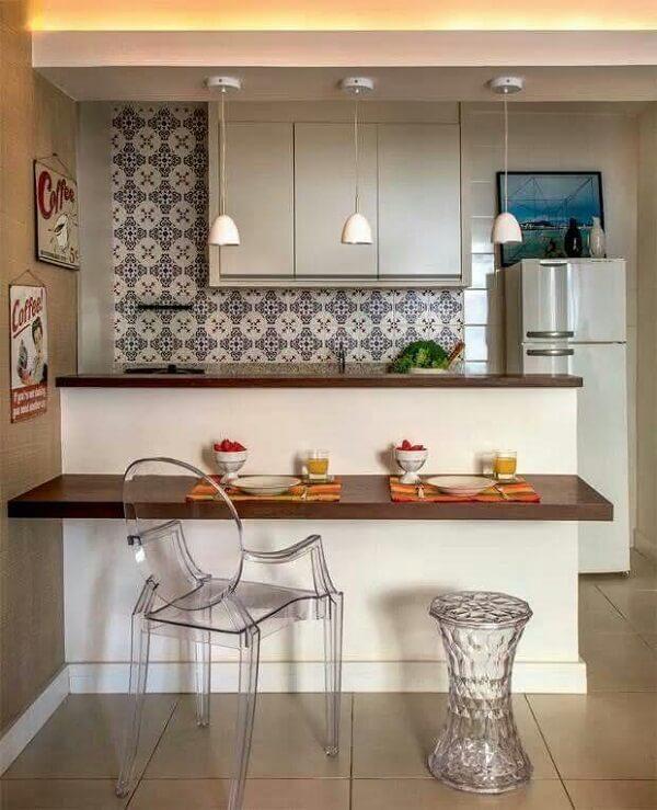 A sanca de gesso com rebaixamento na bancada de cozinha sustenta três pendentes brancos