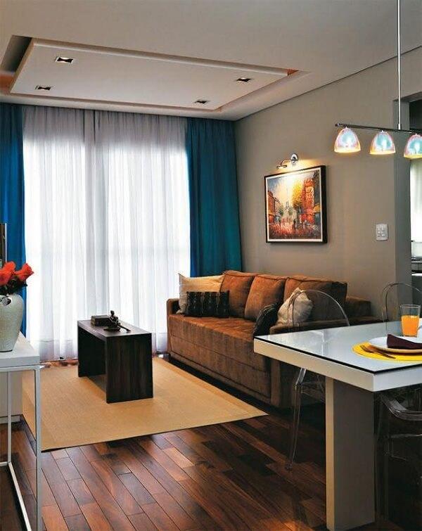 A sanca invertida com recorte no centro decora a sala de estar desse imóvel