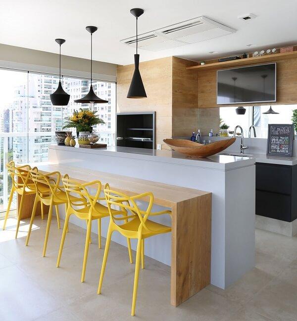 As cadeiras amarelas trazem alegria para a área gourmet rústica