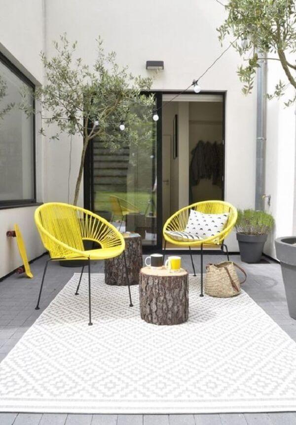 Cadeira de corda amarela se destaca na varanda