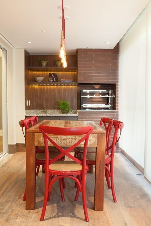 Cadeiras de madeira vermelha e persiana branca decoram a área gourmet rústica simples