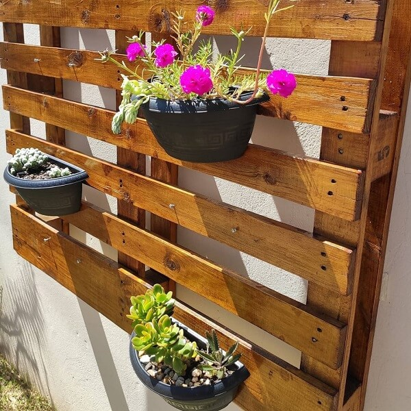 Floreira rústica de parede acomoda flores coloridas
