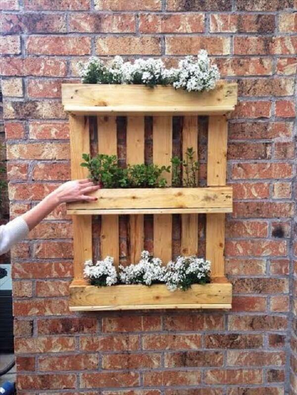 Floreira rústica fixada na parede de tijolinho