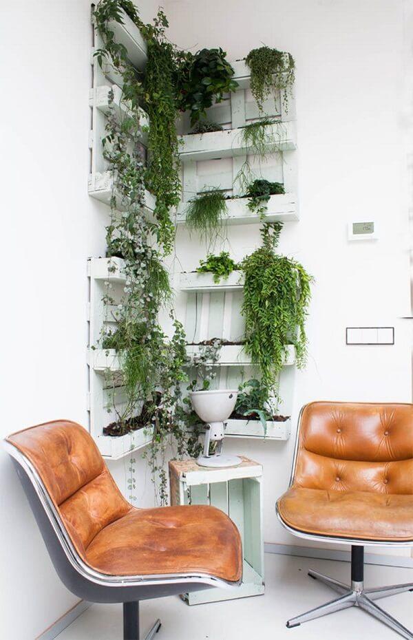 Floreira vertical de parede feita com pallets decoram o cantinho do escritório