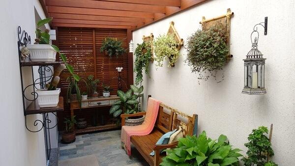 Jardim de inverno no quarto com pergolado, banco e aparador de madeira