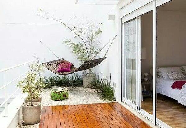 Jardim de inverno no quarto de casal com rede e deck de madeira