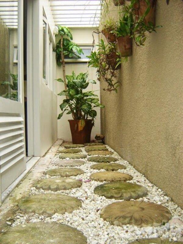 Jardim de inverno no quarto simples com vasos de parede e caminho de pedra