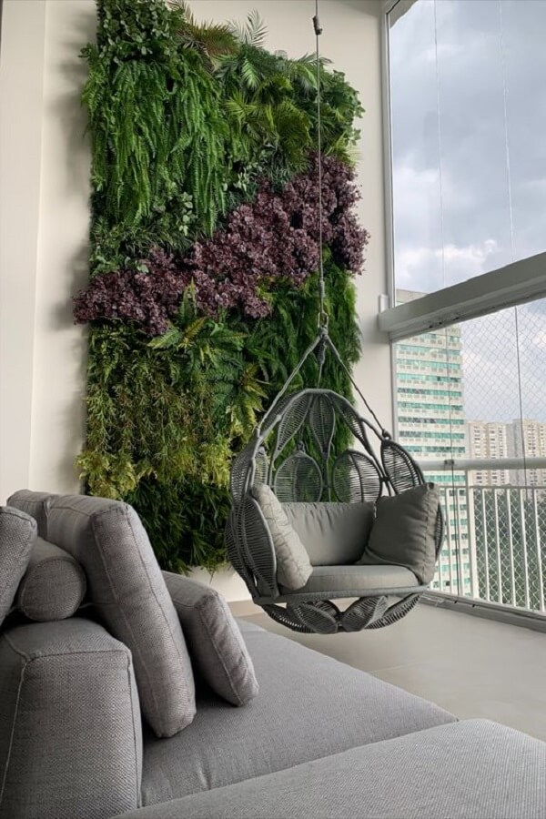 Jardim vertical e cadeira de corda balanço decoram a varanda