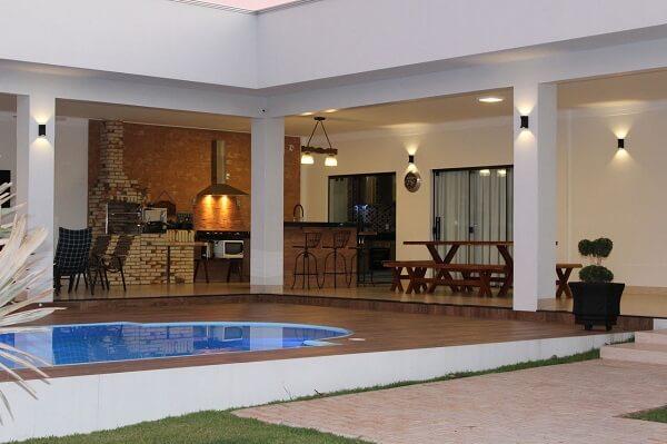 Luminárias metálicas pretas e banquetas de madeira decoram a área gourmet rústica com piscina