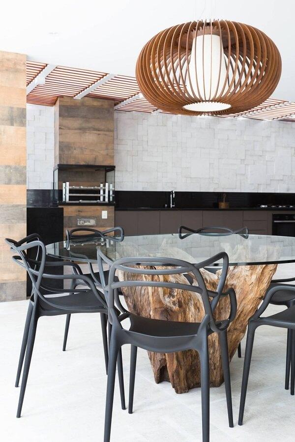 Mesa com tampo de vidro e cadeiras de plástico decoram a área gourmet rústica moderna