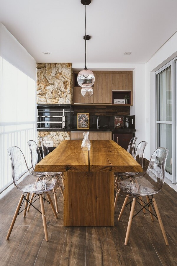 Mesa de madeira e cadeiras de acrílico para a área gourmet rústica