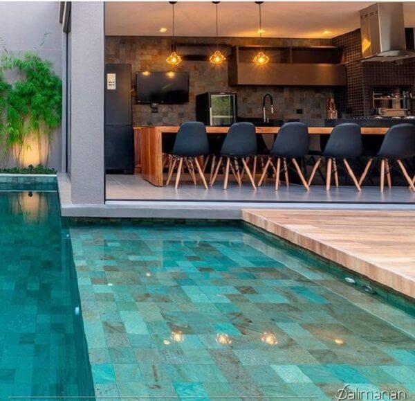 Mesa de madeira extensa para área gourmet rústica com piscina