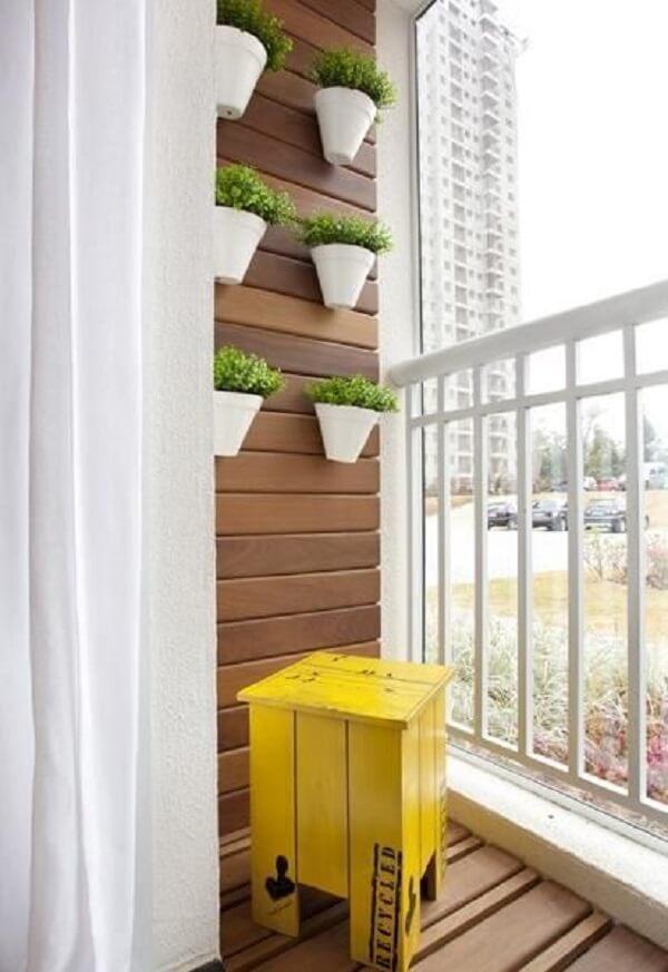 Mesmo as varandas pequenas podem receber a presença de uma linda floreira de parede