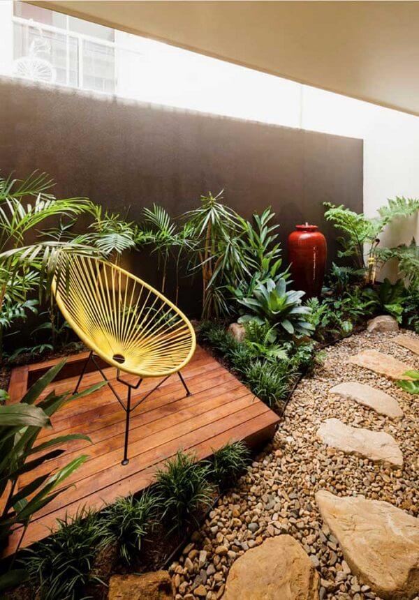 Modelo de jardim de inverno pequeno no quarto com cadeira acapulco amarela