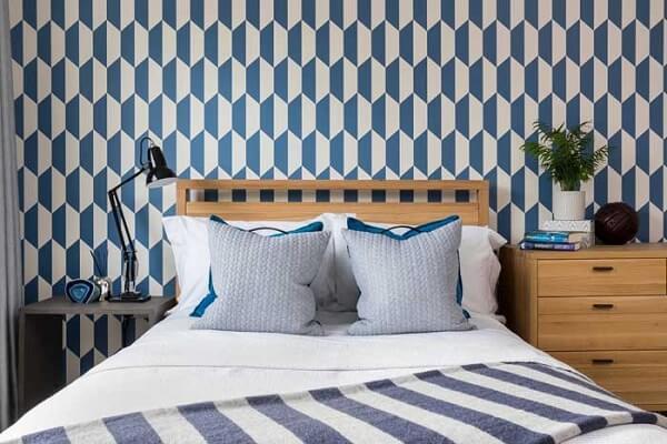 O papel de parede atrás da cama de viúva de madeira valoriza a decoração do quarto