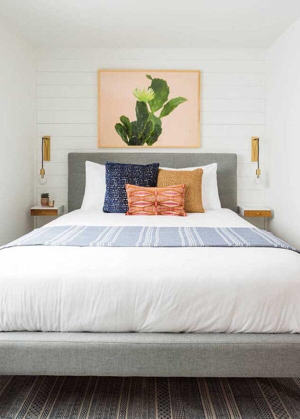 O quadro centralizado no meio da cama de viúva traz charme para a decoração