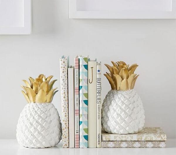 O abacaxi em cerâmica faz sucesso como aparador de livros