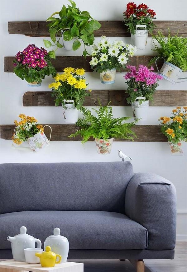 Para decorar a sala nada melhor do que flores e folhagens suspensas em uma linda floreira rústica de parede