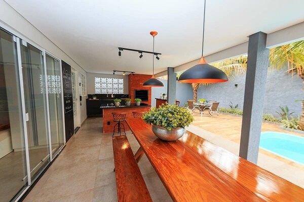 Quem senta na mesa de madeira com banco tem vista para a piscina