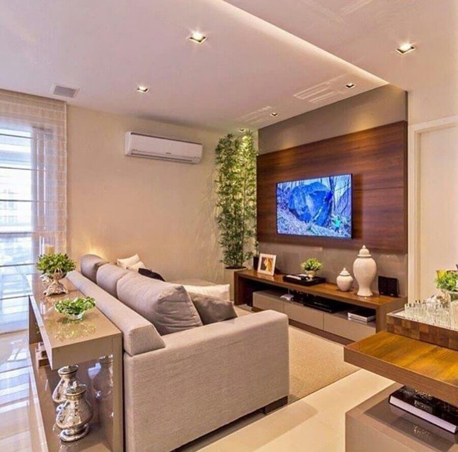 TV na parede da sala com painel de madeira e sofá cinza Foto Pinterest
