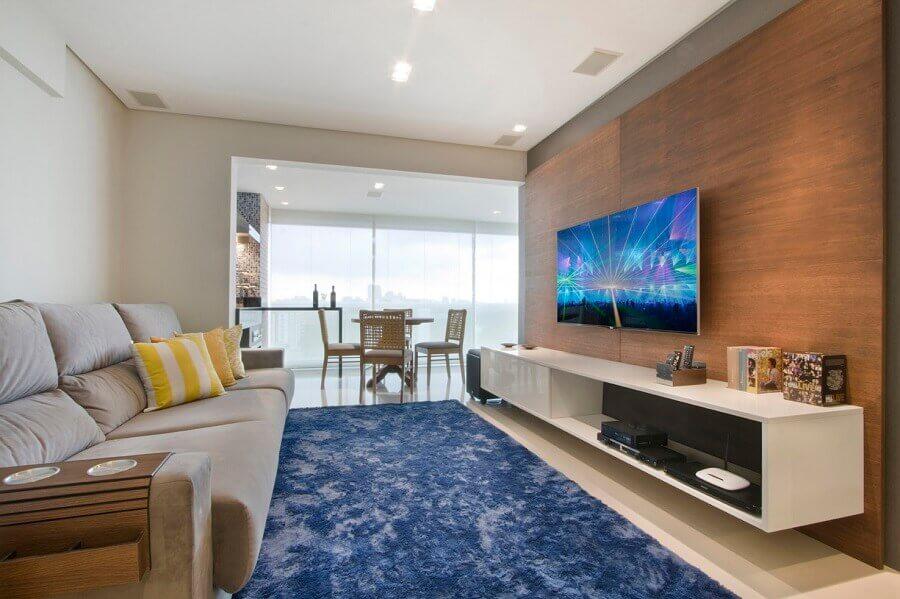 TV na parede da sala com painel de madeira e tapete azul Foto Pinterest