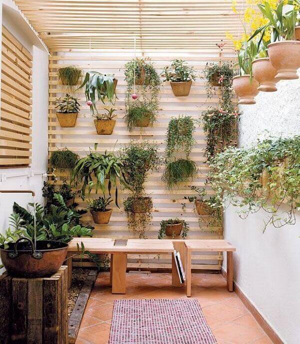 Modelo de jardim de inverno no quarto com pergolado e vasos suspensos