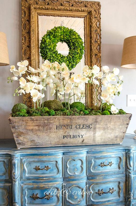Aparador azul com vaso de orquídea branca