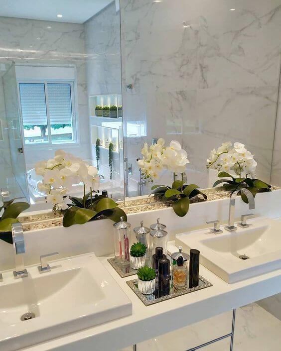 Banheiro com vaso de orquídea branca