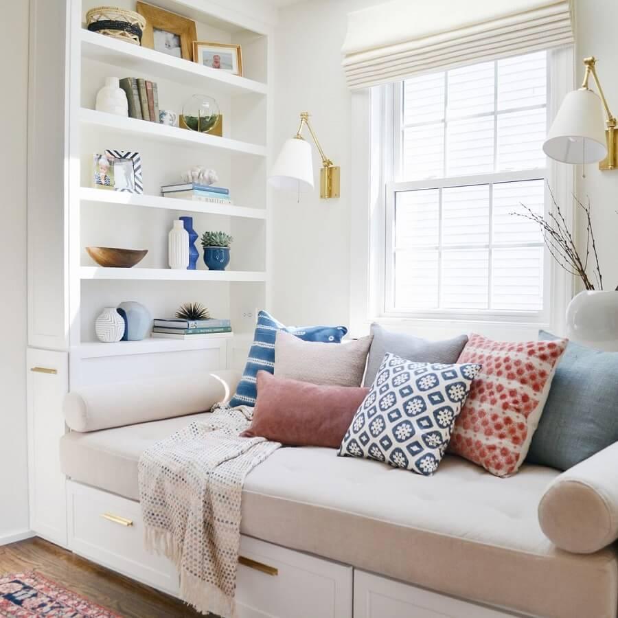 Cantinho de leitura confortável decorado com várias almofadas e luminária de parede para leitura - Foto: Pinterest