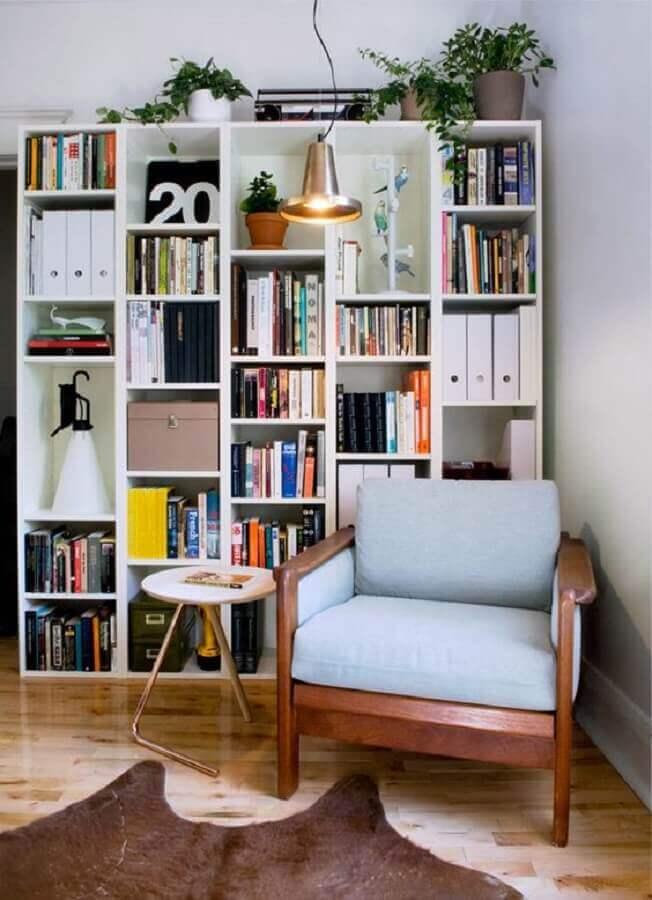 cantinho de leitura decorado com poltrona de madeira e estante de nichos Foto Pinterest