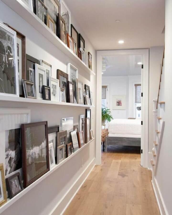 corredor decorado com prateleira para fotos e quadros Foto House Beautiful