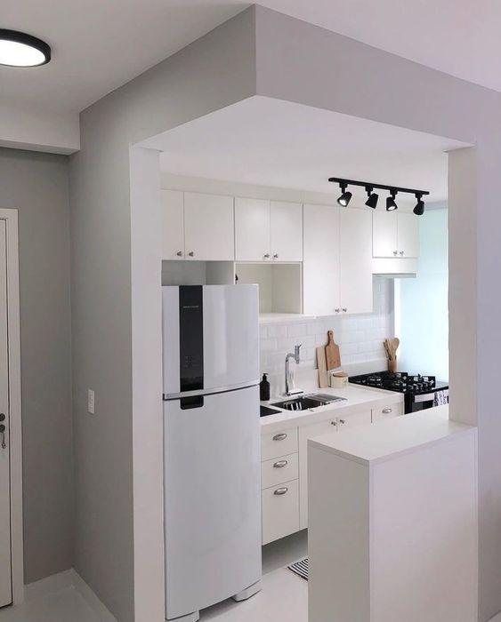 Cozinha com geladeira branca e armários off white