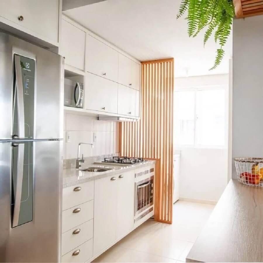 cozinha de apartamento planejada branca com divisória de madeira  Foto Boreal Arquitetura