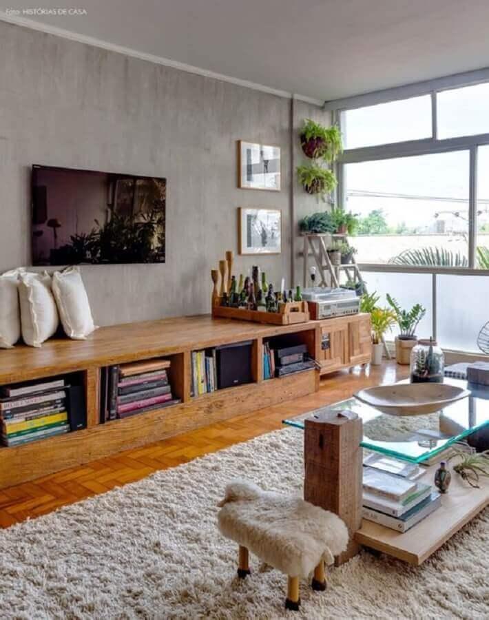 decoração com rack de madeira em sala com TV na parede de cimento queimado Foto Histórias de Casa