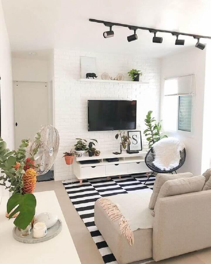 decoração com tapete preto e branco e TV direto na parede de tijolinho branco da sala Foto Casa de Valentina