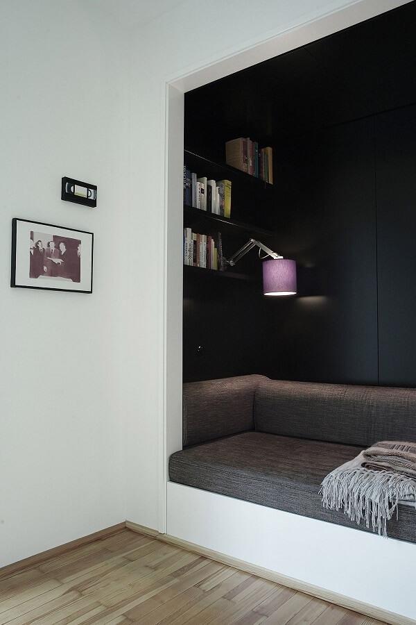 decoração moderna para cantinho de leitura com paredes pretas e luminária de parede para leitura Foto BusyBoo