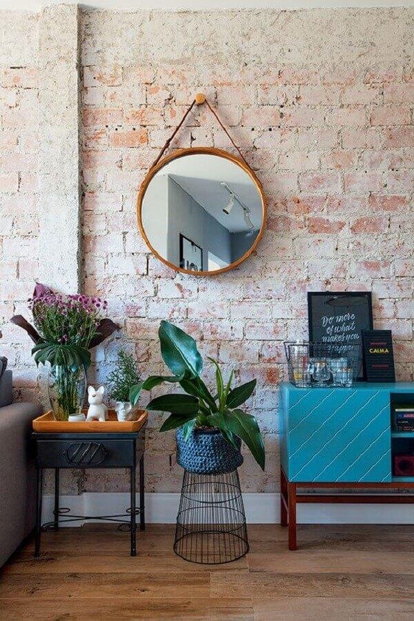 decoração para sala com parede rústica e moldura para espelho redondo de pendurar Foto Jeito de Casa