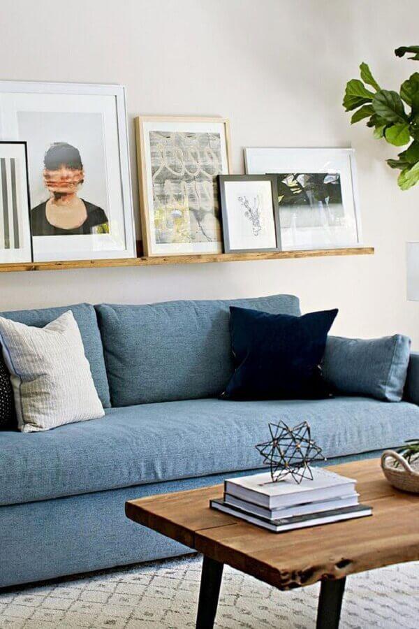 decoraçao de sala com sofá azul e prateleira para quadros de madeira Foto Better Homes and Gardens