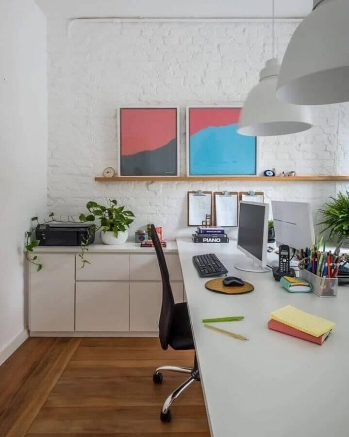 escritório decorado com parede de tijolinho branco e prateleira para quadros de madeira Foto SP Estúdio