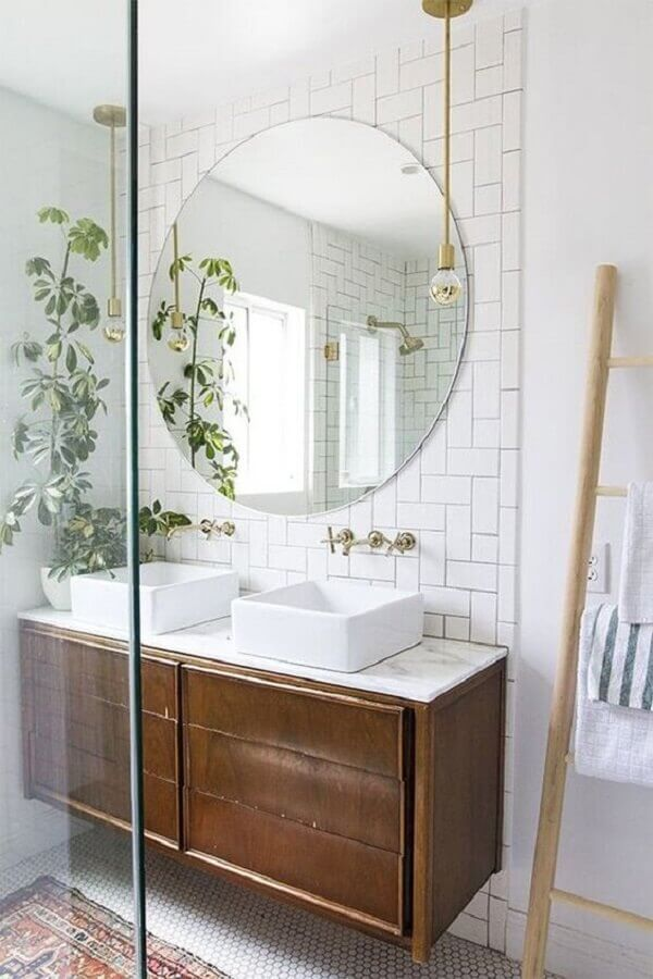 espelho redondo para banheiro decorado com revestimento branco e gabinete suspenso de madeira Foto PURE Design Inc.
