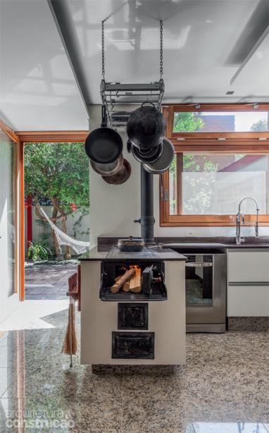 Cozinha com fogão a lenha de ferro na bancada
