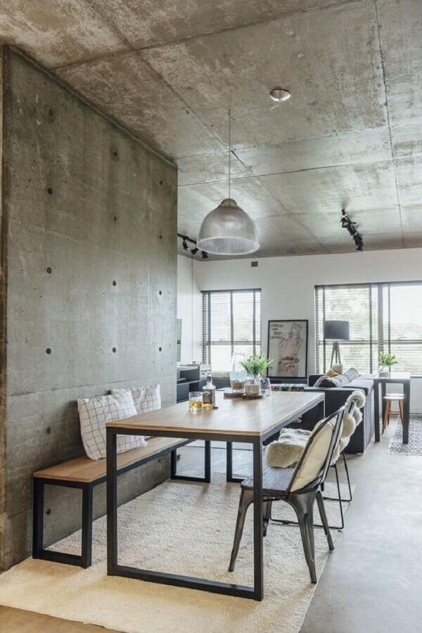 mesa industrial com banco para sala de jantar decorada com revestimento de cimento queimado  Foto HomeWorldDesign