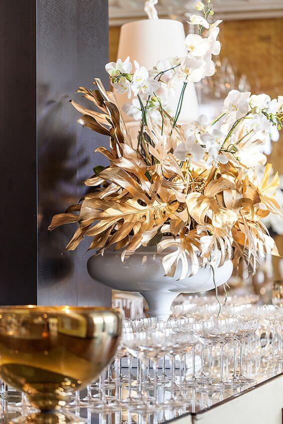 Decoração com orquídea branca e planta costela de adão dourada