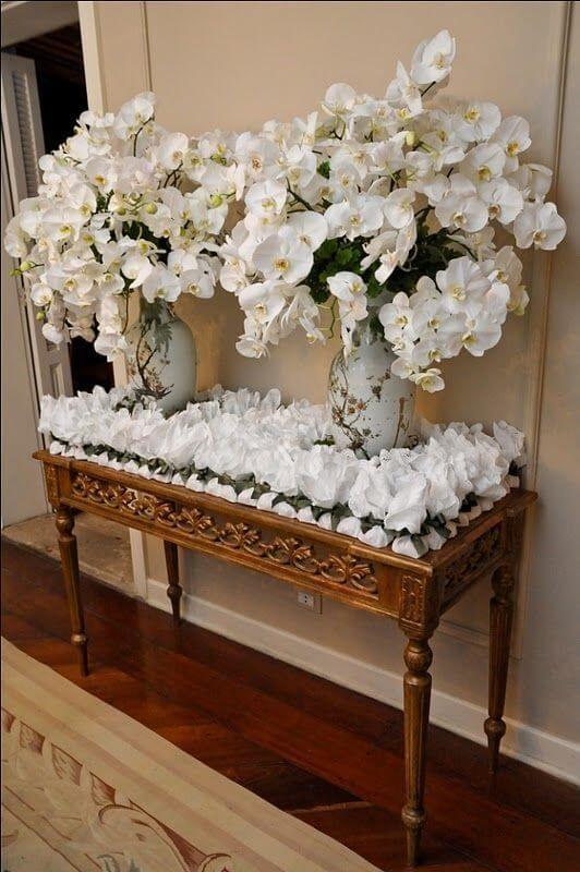 Aparador decorado com arranjo de orquídea branca