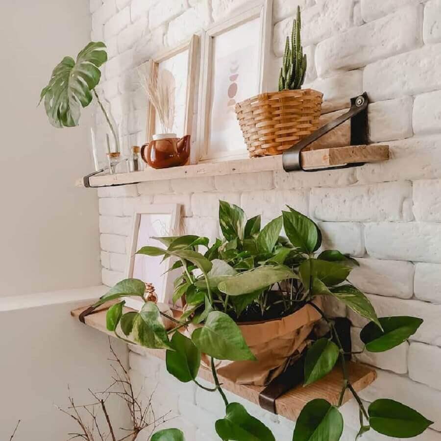 parede de tijolinho branco decorada com vasos em prateleiras de madeira Foto AP da Cacau