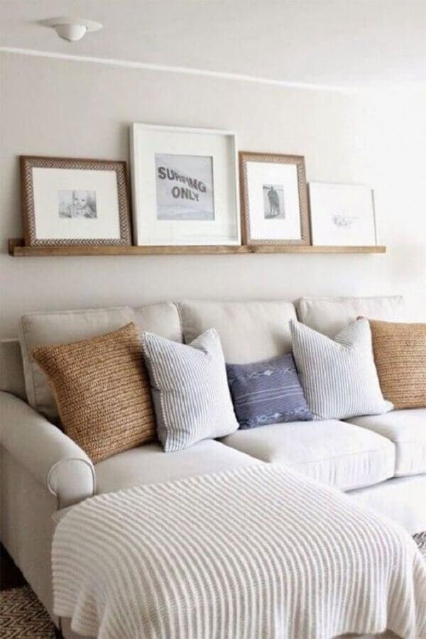 prateleira de madeira para quadros em sala decorada com sofá com chaise Foto Maison Numen
