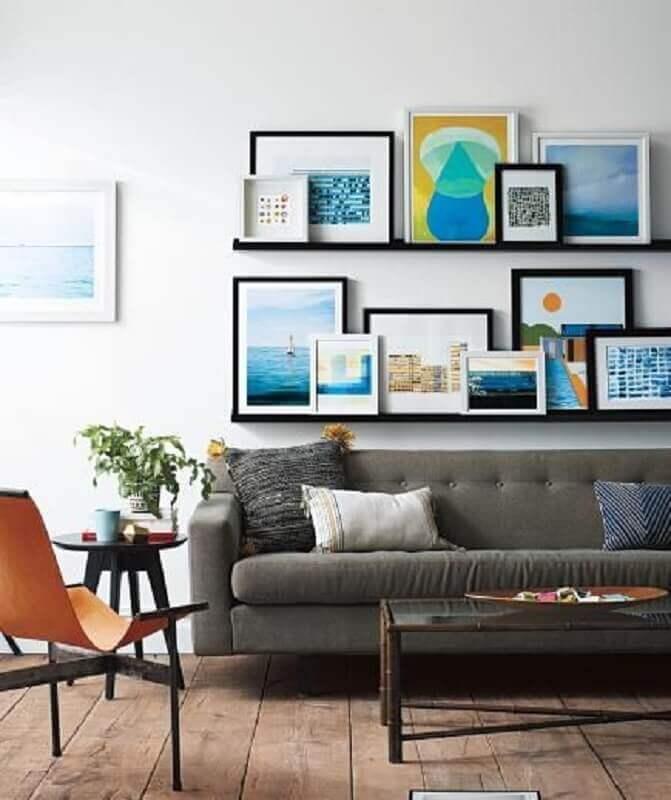 prateleira para quadros sala com sofá cinza e mesa lateral preta Foto Carro de Mola